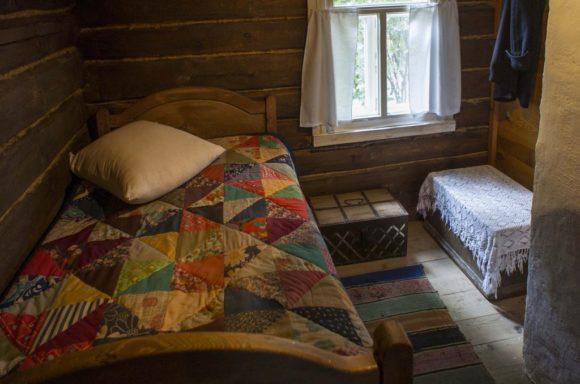 В прихожей — уголок поэта. У окна — деревянная кровать с одеялом из пёстрых лоскутов. Рядом — сундучок, хранивший книги любимых писателей.