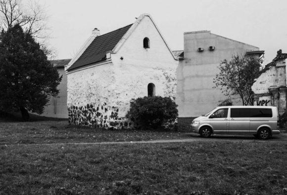 А это старейшей каменной постройкой Выборга. Сложенный из необработанных камней валунов дом был построен в XIV веке Дом купеческой гильдии Его владельцем, по преданию, был некий купец, а позднее дом перешёл к купеческой гильдии. В доме одна большая комната, в которой средневековые купцы заключали свои сделки, и обширный подвал для хранения товаров. На второй этаж дома, где располагались жилые помещения, вела наружная лестница. Постепенно уровень земли поднимался и, через некоторое время, первый этаж оказался ниже уровня мостовой, фактически превратившись в подвал. Дом стал одноэтажным.