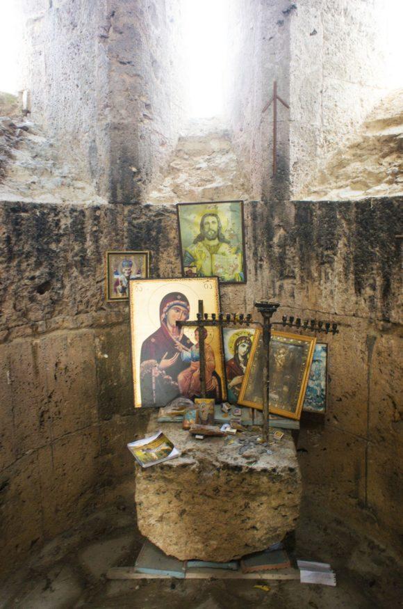 """Внутри грузинской православной церкви стоит несколько икон. Обратите внимание на крест на стене, такие кресты используются в Грузии так же часто, как """"классические"""". Крест святой Нины (груз. ჯვარი ვაზისა — крест [из] виноградной лозы) — христианская реликвия, крест, сплетённый из виноградных лоз, который, по преданию, Богородица вручила святой Нине перед тем, как направить её в Грузию."""